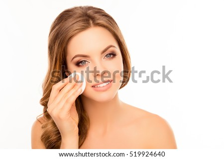 Young pretty woman taking off her makeup with cotton wipe
