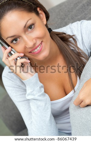 young pretty woman talking on mobile at home