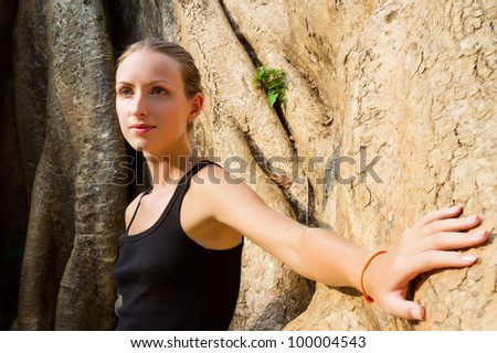 Young pretty woman touching a giant banyan tree in Angkor Wat complex. Focus on face.