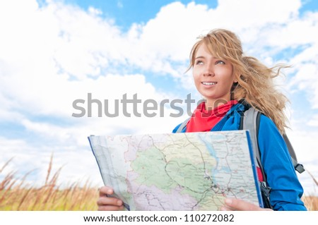 Young pretty woman tourist standing in wheat field with map. Blue cloudy sky in background behind girl. Tourism travel and hiking outdoor in summer. Healthy lifestyle.