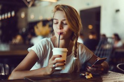 Young pretty woman using smartphone in cafe, drink coffee in cup, sweet breakfast, happy face, outdoor hipster portrait, fashion girl, table, sweet drink, tasty tea, aromatic coffee, smoothie health