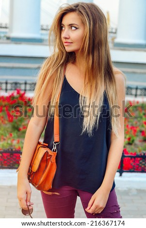 Young pretty woman walking alone at nice sunny day, white city background. Have long trendy blonde ombre hairs,