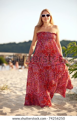 Young pretty woman walking on beach on summer day