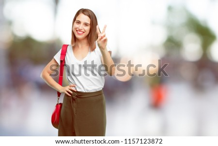 young pretty woman with a proud, happy and confident expression; smiling and showing off success while gesturing victory, giving an