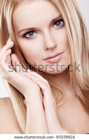 Young pretty woman with beautiful blond hair and multicolor makeup isolated on white background