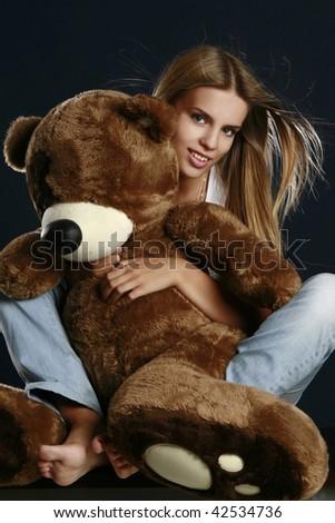Young pretty woman with big teddy bear posing in studio.