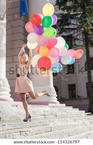 Young pretty woman with colorful latex balloons, urban scene, outdoors
