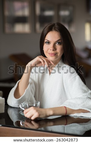 Young pretty woman with cup of green tea in the rest room at the hotel spa