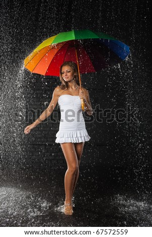 Stock Photo Young pretty woman with multi-coloured umbrella under rain on a black background.