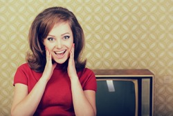 Young pretty woman with oldfashioned hairstyle happy smiling with surprise looking at camera, at room with vintage wallpaper and retro TV set, stylization 60-70s. Self isolation, quarantine, stay home