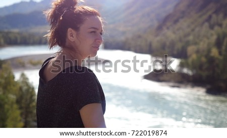 Young pretty woman with red hair relaxation in the beautiful mountains and mountain river view