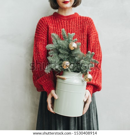 Young pretty woman with red knitted sweater holding in her hands vintage mint watering pot with christmas fir branches decorated with gold balls. Minimal styled christmas and new year concept.