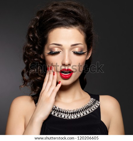 Young pretty woman with red manicure,  lips and creative eye makeup.  Fashion model with bright expressions