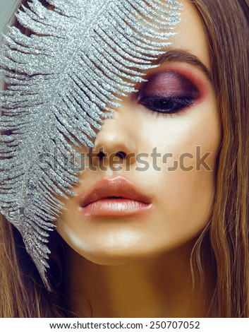 young pretty woman with silver feather like ice decoration to new year, face close up, weathered lips winter