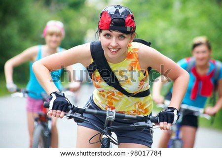 Young pretty women  race on bicycle in green park