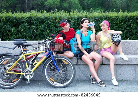 Young pretty women resting after cycle race in the green park