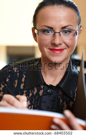 Young pretty writer woman with orange book in hands