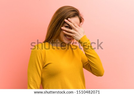 Young pretty young woman blink at the camera through her fingers, embarrassed covering her face.