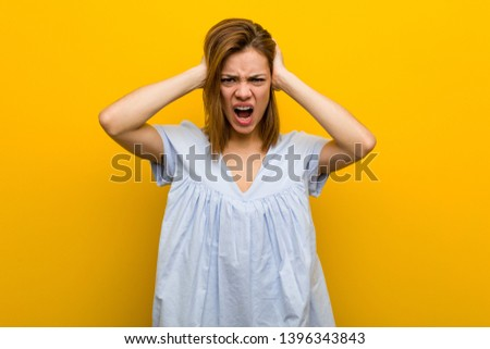 Young pretty young woman covering her ears with hands trying not to hear too loud sound.