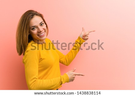 Young pretty young woman excited pointing with forefingers away.