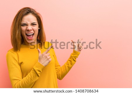 Young pretty young woman pointing with forefingers to a copy space, expressing excitement and desire.