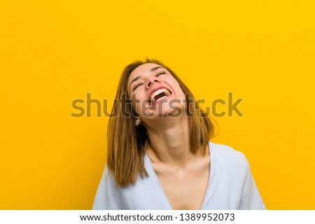 Young pretty young woman relaxed and happy laughing, neck stretched showing teeth.