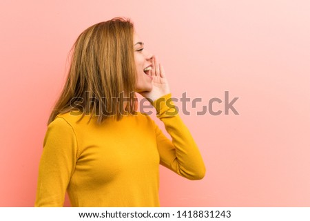 Young pretty young woman shouting and holding palm near opened mouth.
