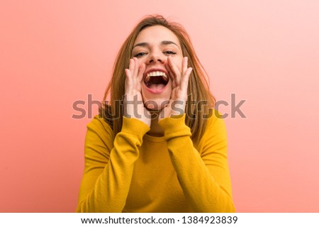 Young pretty young woman shouting excited to front.