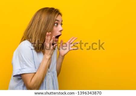 Young pretty young woman shouts loud, keeps eyes opened and hands tense.