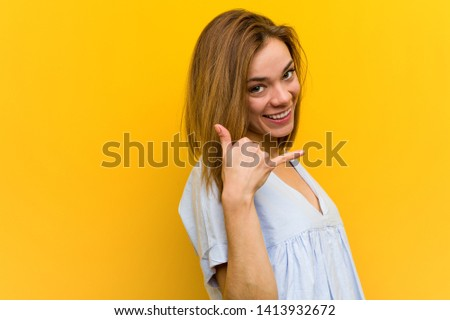 Young pretty young woman showing a mobile phone call gesture with fingers.