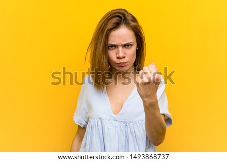 Young pretty young woman showing fist to camera, aggressive facial expression.