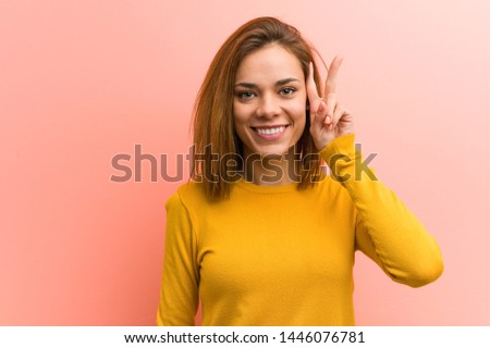 Young pretty young woman showing victory sign and smiling broadly.
