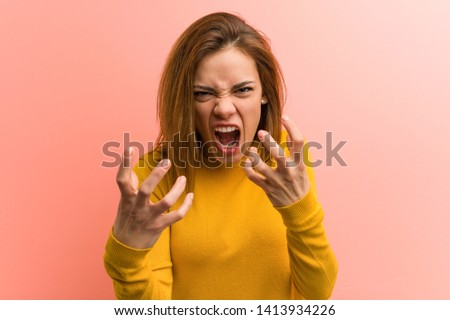 Young pretty young woman upset screaming with tense hands.