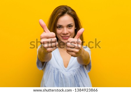 Young pretty young woman with thumbs ups, cheers about something, support and respect concept.