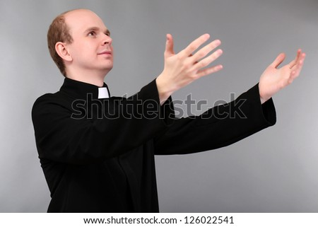 Young priest on gray background