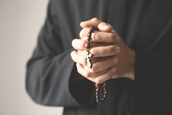 Young priest with rosary beads on light background, closeup