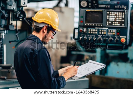 young profession technician engineer operate heavy machine to automated CNC in factory, worker with check list. Stock photo ©