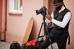 Young professional african american videographer holding professional camera with pro equipment. Afro cameraman wearing black duraq and face protect mask, making a videos.