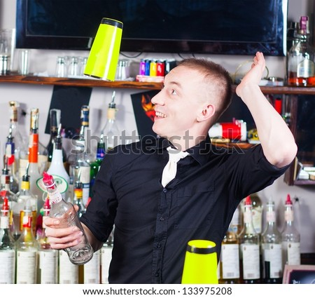 Young professional barman in action with shaker making cocktail drinks
