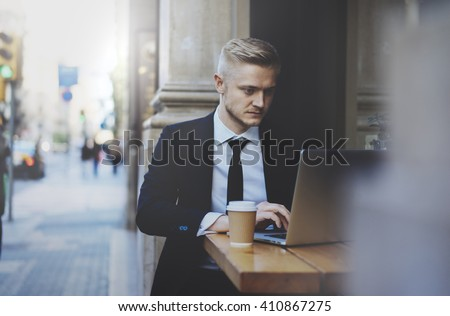 Young professional businessman wearing suit and using modern laptop outdoors, successful manager working in cafe during break and searching information in internet on his portable computer
