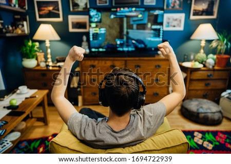 Young professional esport gamer with headphones playing and winning competitive internet MMORPG cyber championship in first person shooter strategy online video game on high end computer gaming rig