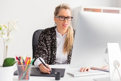 Young professional female designer working with computer