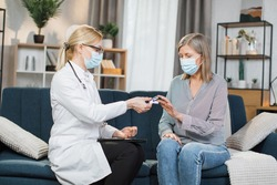 Young professional female doctor or nurse wearing protective mask, measuring saturation with pulse oximeter, while visiting her senior lady patient at home. Coronavirus covid 19 pandemic concept.