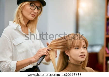 young professional hairdresser doing creative stylish hair cut in beauty saloon. styler, hairdo and client