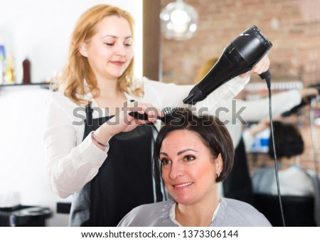 Young professional hairdresser is combing and drying hair to smiling woman in hairdress salon.