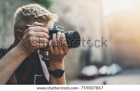 Young professional male videographer shooting outdoor on modern camera, empty area with copy space for your content, design or text message, flare light effect, man photographer taking photo outdoor