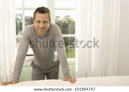 Young professional man leaning on a sofa in a property's living room, next to large windows.