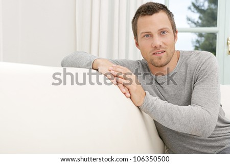 Young professional man sitting on a white sofa at home, smiling.