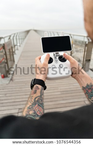 Young professional or amateur photographer or drone pilot holds remote control panel with screen and controls ready to fly quadrocopter in air to see birds point of view.Hipster user of new technology #1076544356