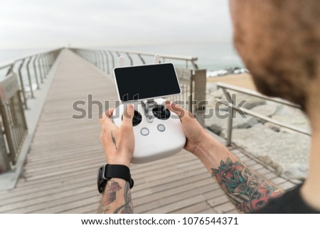 Young professional or amateur photographer or drone pilot holds remote control panel with screen and controls ready to fly quadrocopter in air to see birds point of view.Hipster user of new technology #1076544371
